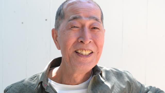 笑顔の日本の先輩男性のヘッドショット肖像画 - 男性 笑顔点の映像素材/bロール