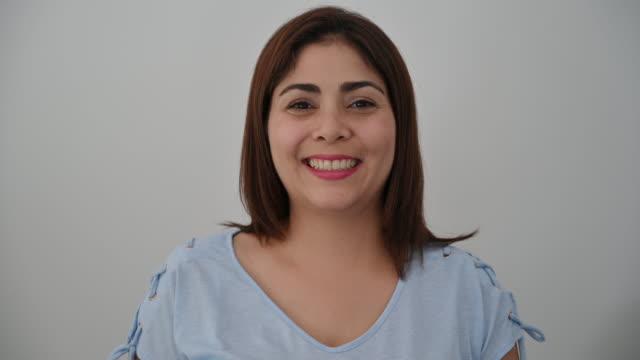 Headshot portrait of smiling mature Latin American woman