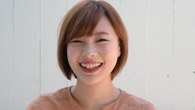 笑顔の若い日本人女性のヘッドショットの肖像画 - 美人点の映像素材/bロール
