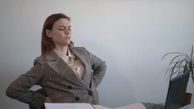 hälsa, lider attraktiv affärskvinna av ryggsmärta på grund av felaktig hållning när du sitter vid datorn medan du arbetar på kontoret, smärta i ryggraden - människorygg bildbanksvideor och videomaterial från bakom kulisserna