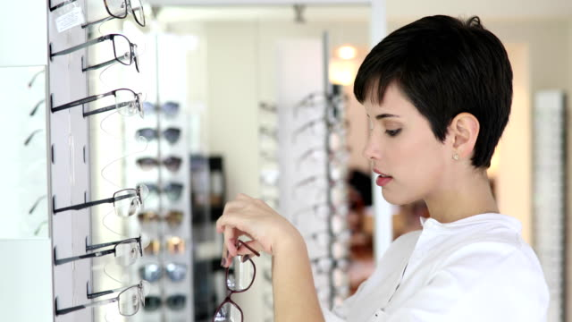 health care, eyesight and vision concept - happy woman choosing glasses at optics store video