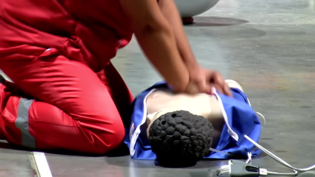 Health care worker performing CPR on mannequin side view