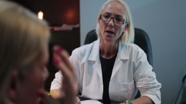 stockvideo's en b-roll-footage met gezondheidszorg werknemer praten met zieke senior patiënt in het ziekenhuis - blond haar