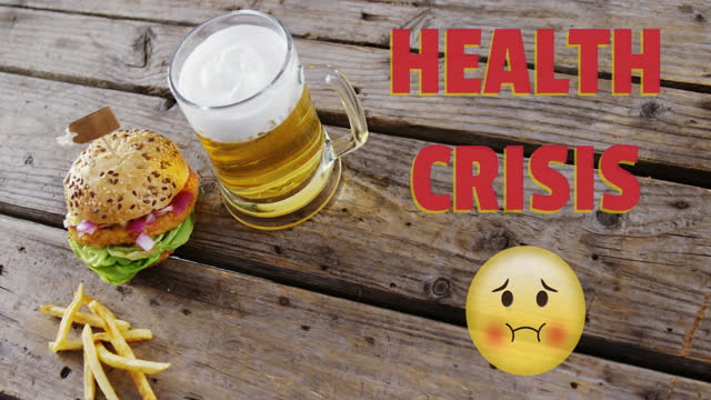 Health Crisis text and  Nauseated Face Emoji against beer, burger and fries on wooden surface