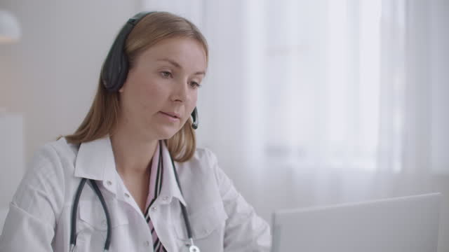 health professional woman is consulting patients by telephone, using headphones with microphone, distant consultation
