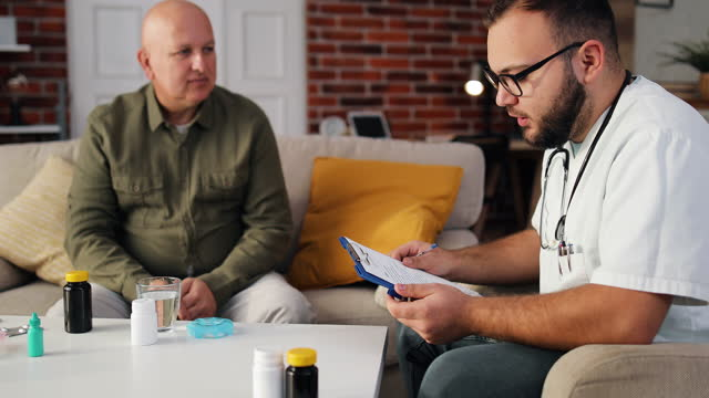 Health visitor and a senior man during home visit. A male nurse or a doctor showing test results on a tablet. Senior patient and caregiver using tablet. video