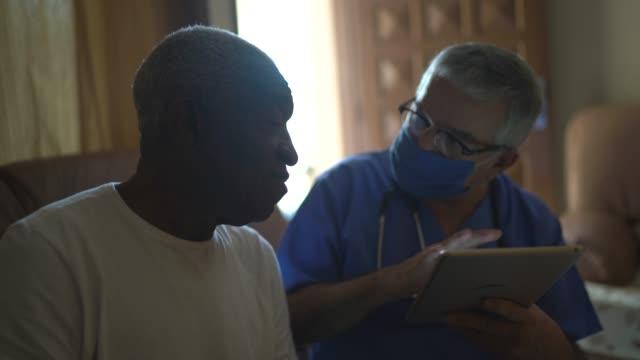 健康訪問者と家庭訪問中のシニア男性 - デジタルタブレットを使用して - 老人ホーム点の映像素材/bロール