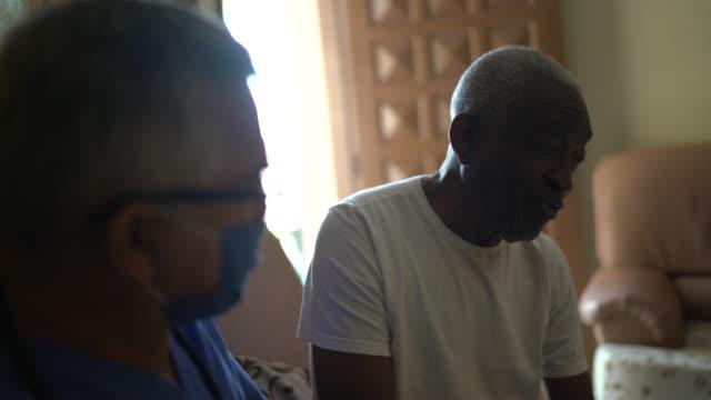 sağlık ziyaretçisi ve ev ziyareti sırasında üst düzey bir adam - ziyaret stok videoları ve detay görüntü çekimi