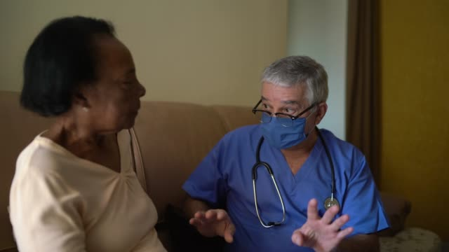 自宅訪問中の健康訪問者と先輩女性 - 老人ホーム点の映像素材/bロール