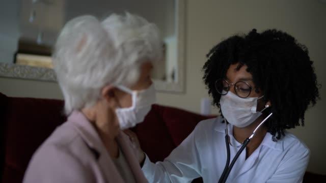 hälsa besökare och en äldre kvinna under hembesök - omsorg bildbanksvideor och videomaterial från bakom kulisserna