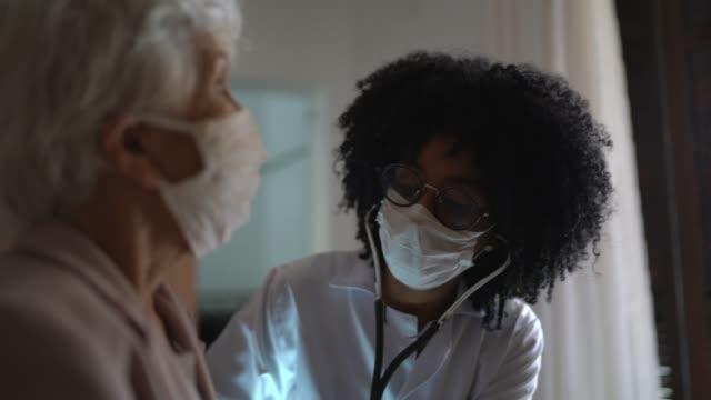 gość zdrowia i starsza kobieta podczas wizyty domowej - serce człowieka filmów i materiałów b-roll