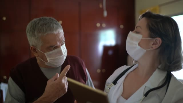 health visitor asking with digital tablet to a senior man during home visit - mask стоковые видео и кадры b-roll