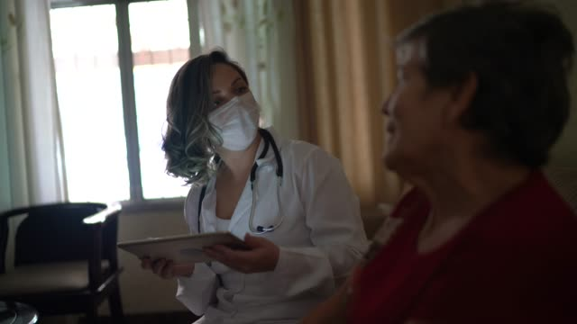health visitor asking with digital tablet to a senior woman during home visit - infermiera personale medico video stock e b–roll