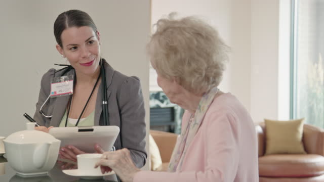 Healthcare Asking Questions of a Senior Woman over Coffee video