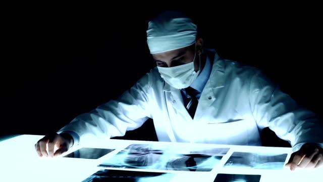 stockvideo's en b-roll-footage met healthcare doctor carefully examining x ray medical concept - alleen één mid volwassen man