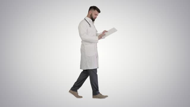 vídeos de stock e filmes b-roll de healthcare, medical concept doctor walking and looking at cardio test results on gradient background - artéria coronária