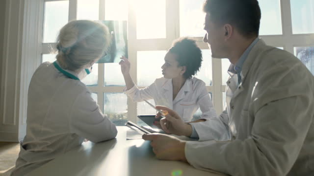 Healthcare, medical: Group of multi-ethnic doctors discuss and looking x-ray in a clinic or hospital. - vídeo