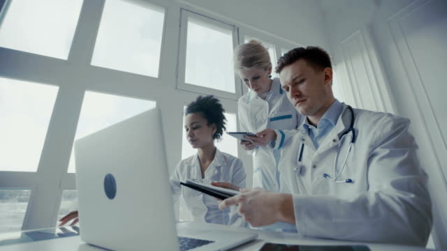 Healthcare, medical: Group of multi-ethnic doctors discuss and looking x-ray in a clinic or hospital. – Video