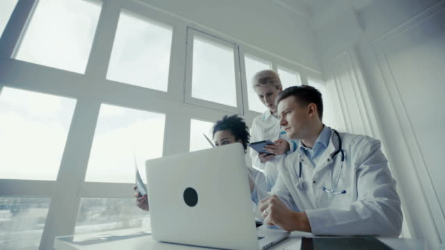 Cuidados médicos, médico: o grupo de doutores multi-ethnic discute e que olha o raio x em uma clínica ou em um hospital. - vídeo