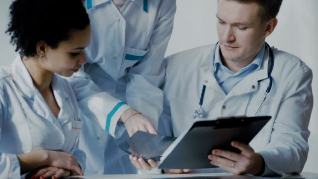 Healthcare, medical: Group of multi-ethnic doctors discussing and looking x-ray in a clinic or hospital. video