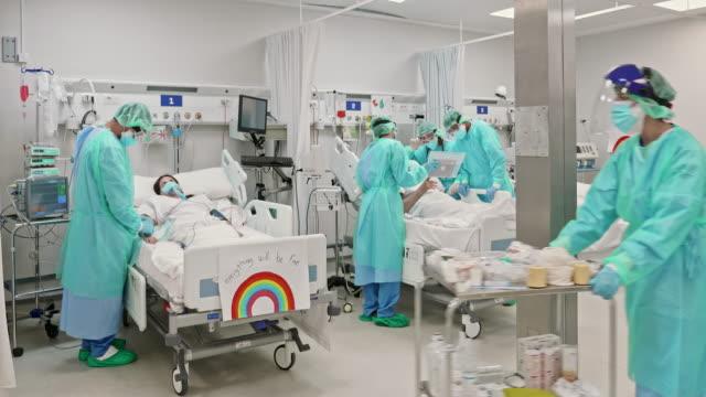 hälso- och sjukvårdspersonal som arbetar på intensiven under pandemin - intensivvårdsavdelning bildbanksvideor och videomaterial från bakom kulisserna