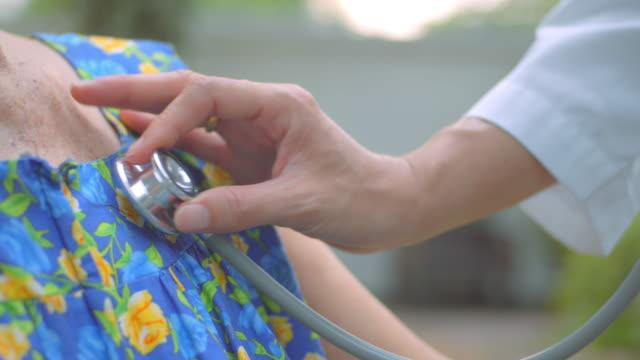 シニアウーマンの心に耳を傾けるヘルスケアプロフェッショナル、クローズアップ - 聴診器点の映像素材/bロール