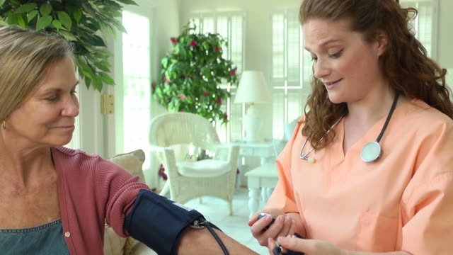 vídeos de stock, filmes e b-roll de profissional da saúde levando a pressão de sangue de mulheres - geriatria