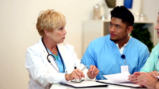 Healthcare professionals in a meeting discussing serious issues video
