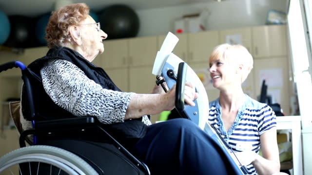 healthcare worker assisting senior woman in physiotherapy exercise - senior care stock videos and b-roll footage