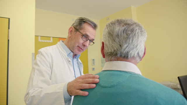 Healthcare worker consoling patient at clinic Male healthcare worker explaining senior man. Smiling medical professional consoling elderly man. They are in clinic during medical exam. general practitioner stock videos & royalty-free footage