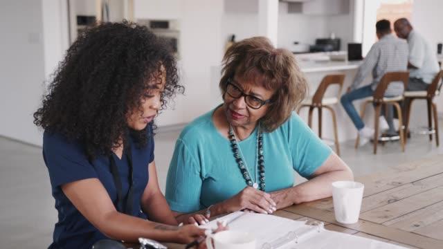 在家訪期間, 醫護人員與一名老年患者一起填寫表格, 視野很高 - 非裔美國人種 個影片檔及 b 捲影像