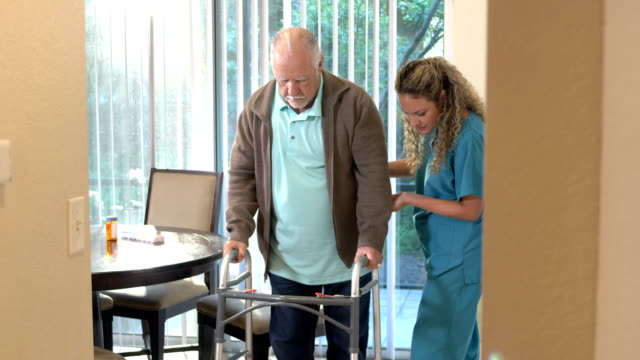 Healthcare worker helping senior man with walker