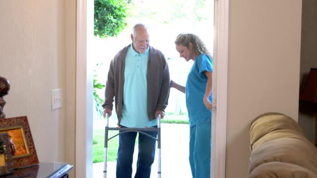 ウォーカーとの高齢者を助けるヘルスケアワーカー - 老人ホーム点の映像素材/bロール