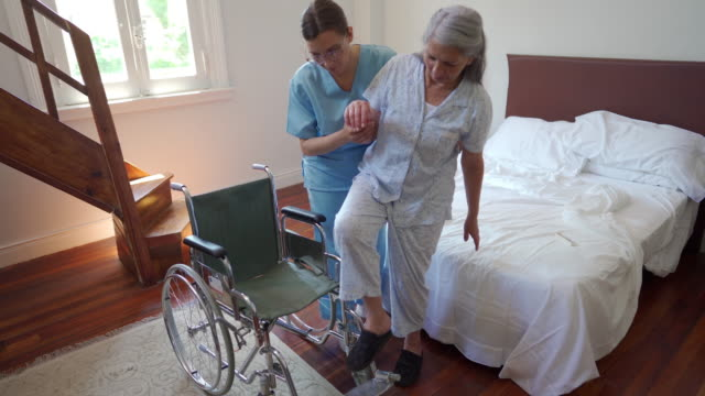 healthcare worker helping senior woman to sit in wheelchair - infermiera personale medico video stock e b–roll