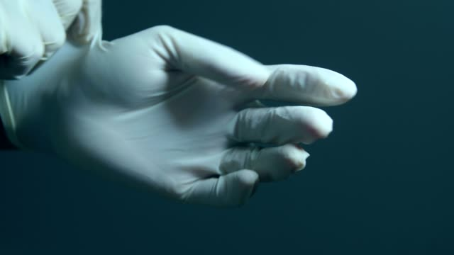 Healthcare worker putting on medical gloves Healthcare worker putting on medical gloves glove stock videos & royalty-free footage
