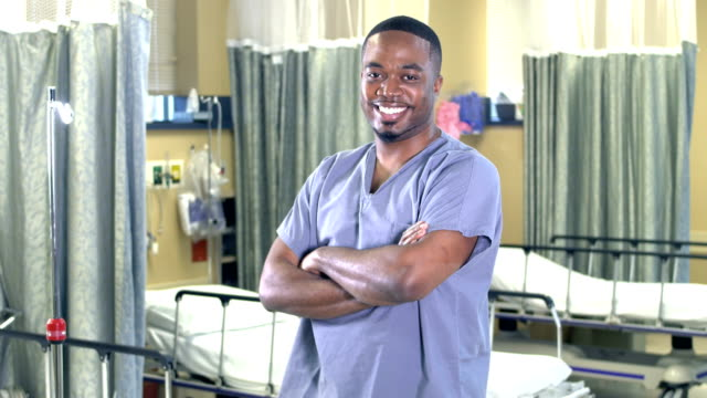 Healthcare worker standing in hospital ward A mid adult African-American man in his 30s wearing scrubs, standing in a hospital ward, smiling at the camera. He is a doctor or a male nurse. stretcher stock videos & royalty-free footage