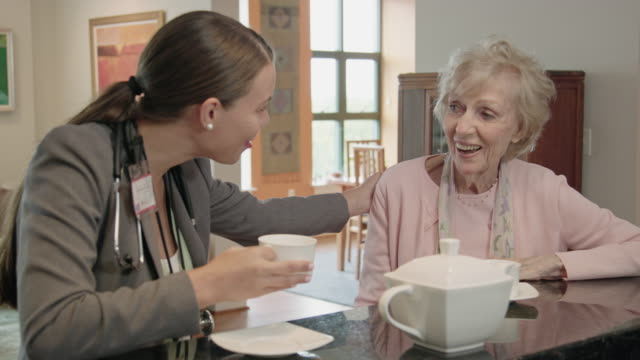 vídeos y material grabado en eventos de stock de trabajador profesional de la salud hablando con altos mujer café - geriatría