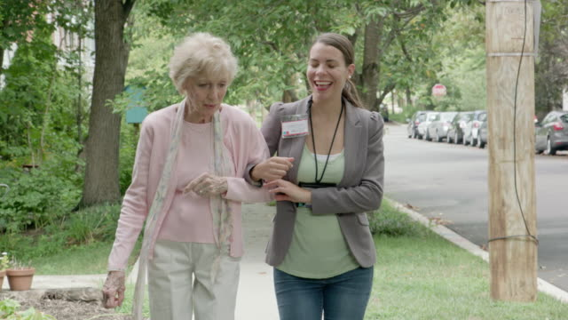Healthcare Worker Walking with Senior Woman Outdoors video