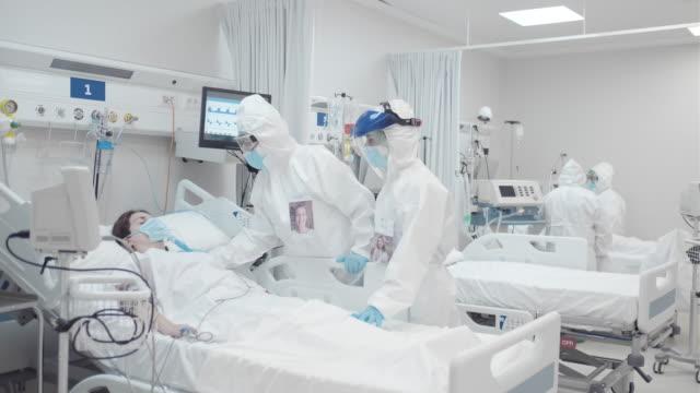 sjukvårdspersonal justerar syrgasmasken till en covid-patient. - intensivvårdsavdelning bildbanksvideor och videomaterial från bakom kulisserna