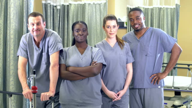 healthcare workers standing in hospital ward - fianco a fianco video stock e b–roll