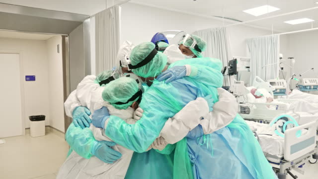 Healthcare workers support each other after a long day at ICU
