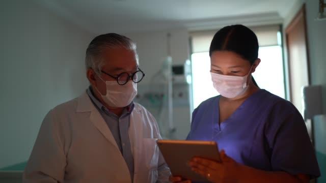 vídeos de stock e filmes b-roll de healthcare workers using digital tablet using face mask in hospital - enfermeira