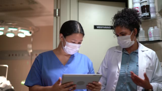 Healthcare workers walking and using digital tablet with face mask in hospital
