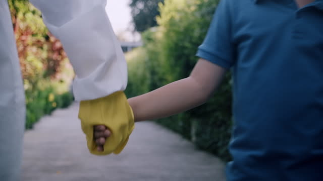 stockvideo's en b-roll-footage met gezondheidszorg die met besmet kind loopt, hand die hem houdt. - bord bericht