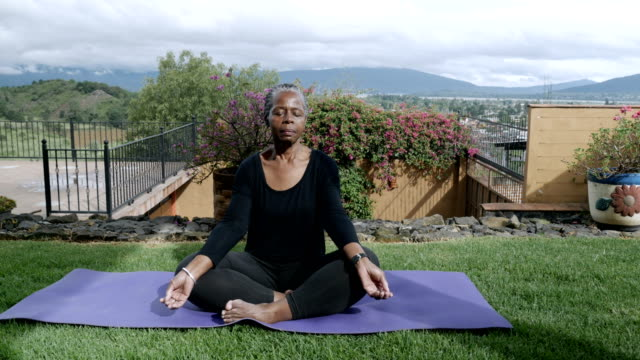 Healthy African American senior sitting cross legged meditating outside Healthy African American senior in 60s sitting cross legged meditating outside on a yoga mat - dolly shot lotus position stock videos & royalty-free footage