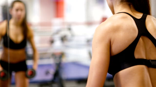 Healthy and well trained woman lifts weights at fitness gym video