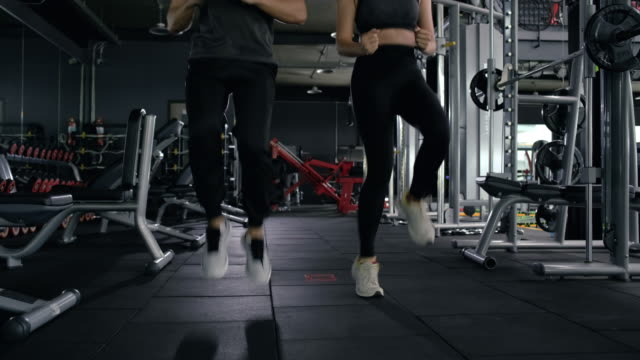 Healthy asian two people young woman with man high knee cardio (HIIT) during exercise burning fat overweight workout training at fitness cross gym healthy lifestyle.