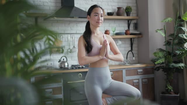 自宅で木のポーズでヨガをしている健康なアジアのヨガの女性 - ヨガ点の映像素材/bロール