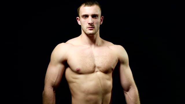 健康的なアスリートが筋肉黒を背景にした - ボディビル点の映像素材/bロール