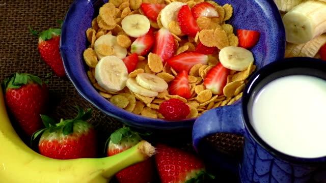 Healthy breakfast. Cornflakes, fresh strawberries, banana and milk video